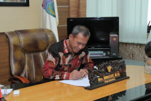 The MAyor signing the handover document